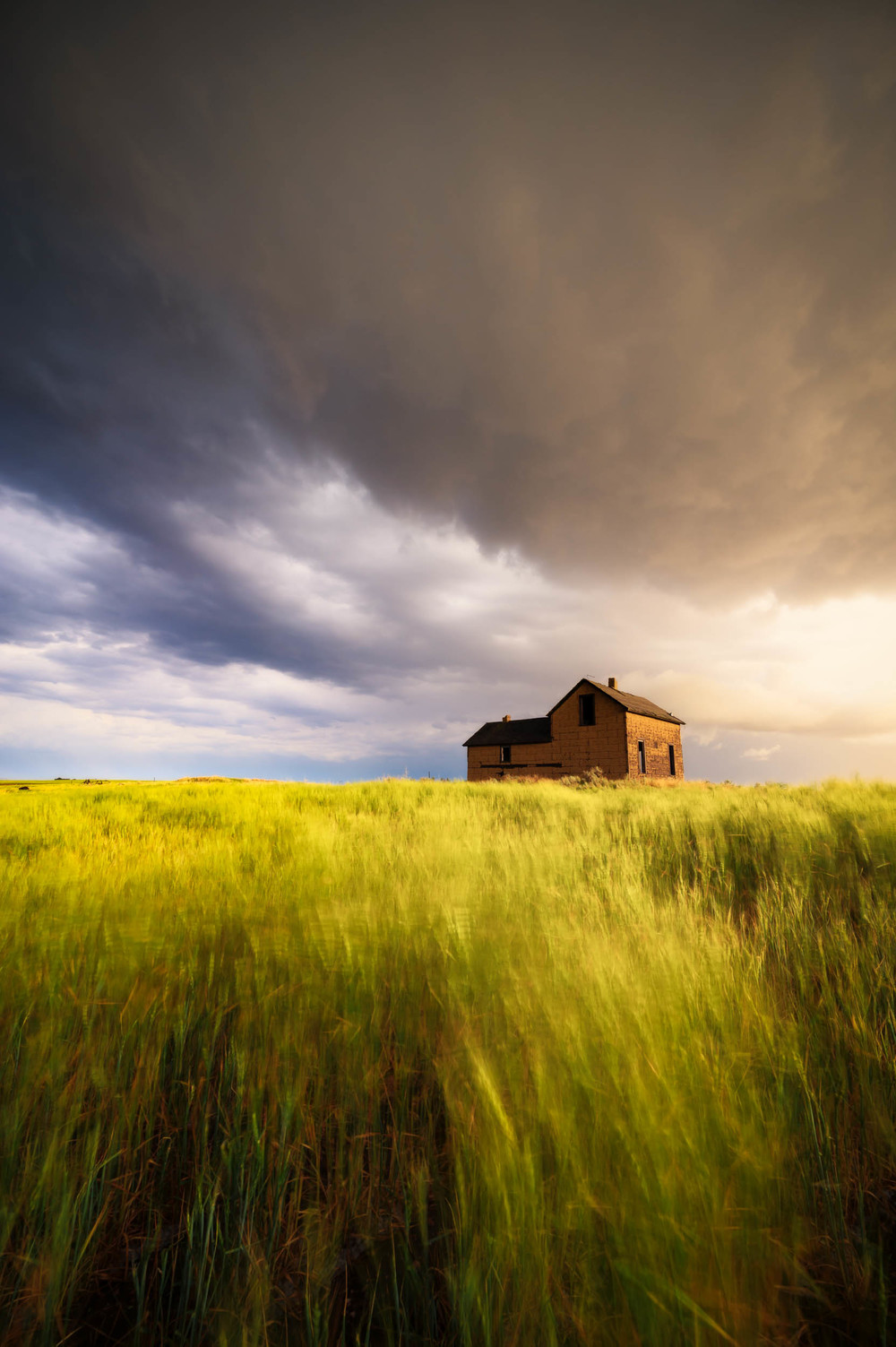 An abadoned farmhouse weathers a storm in rural Wyoming