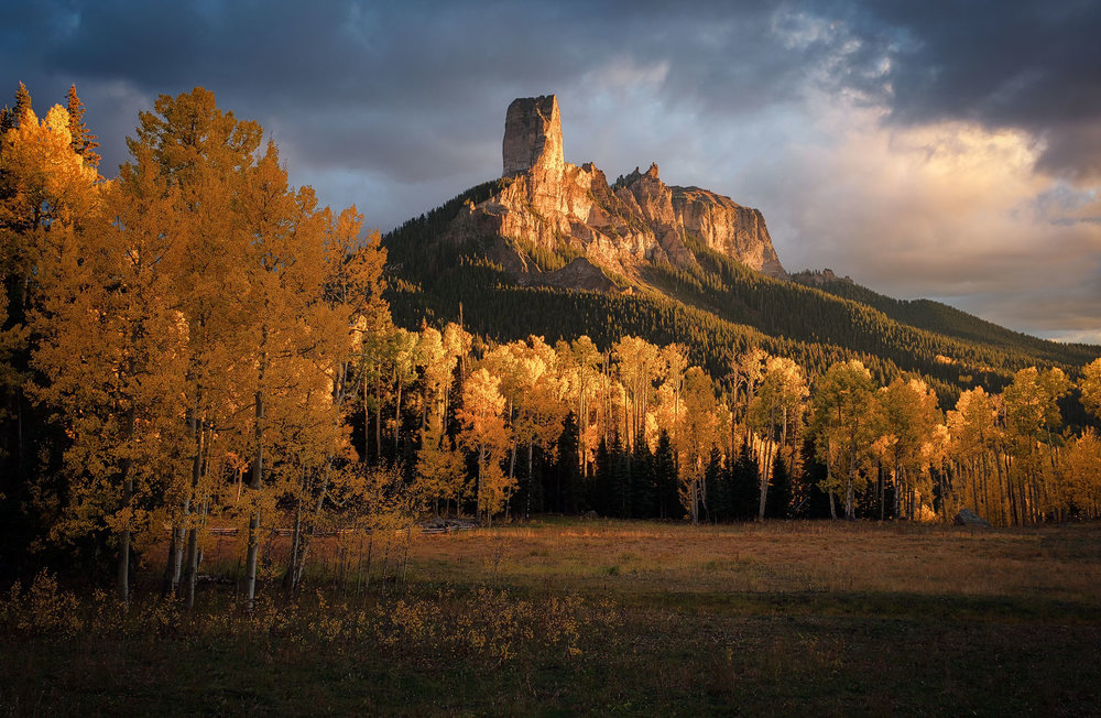 Chimney Rock is illuminated by the last light of the day in the San Juan Mountains of Colorado