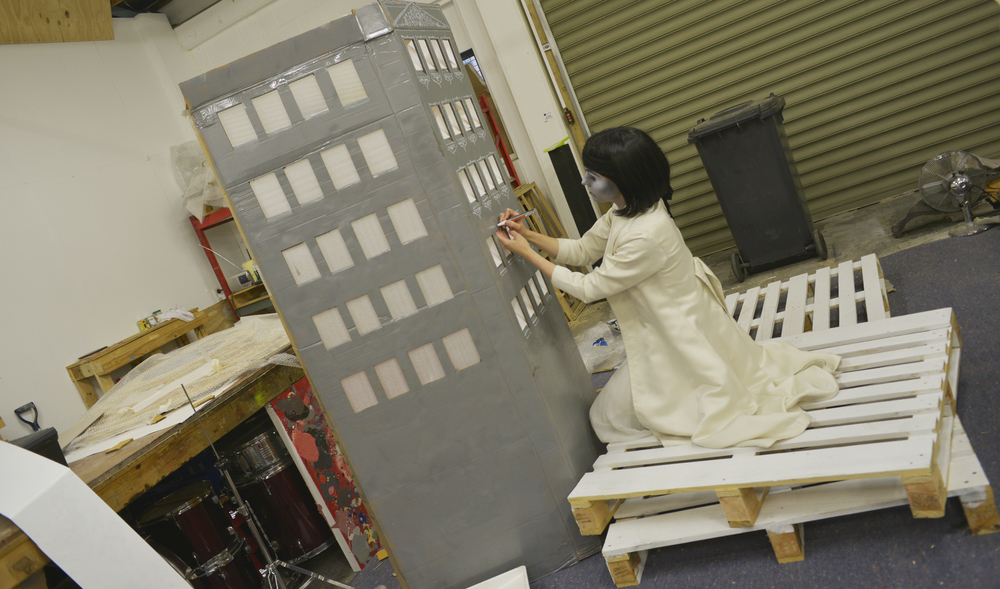 Above:    Carolin  applying a Greco-Art Nouveau touch to the set's buildings.