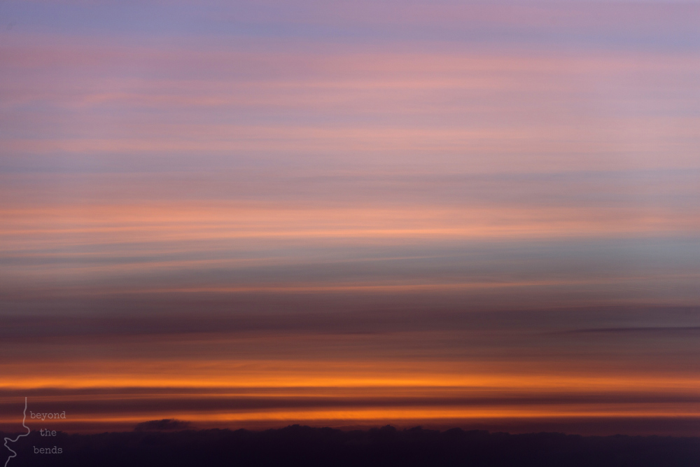 Stripes of clouds provide a canvas for the rising sun.