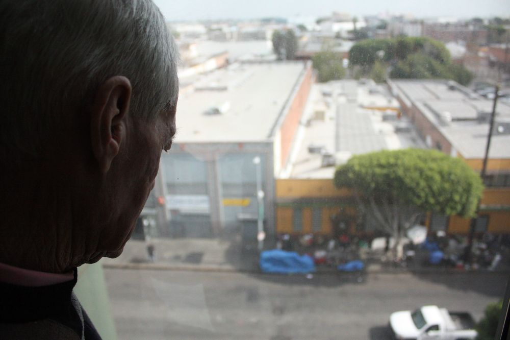 Michael peeks out the window from the 5th floor where he lives with others that have completed the men's program and are transitioning out of the mission. Below, San Pedro, one of the main roads on Skid Row.