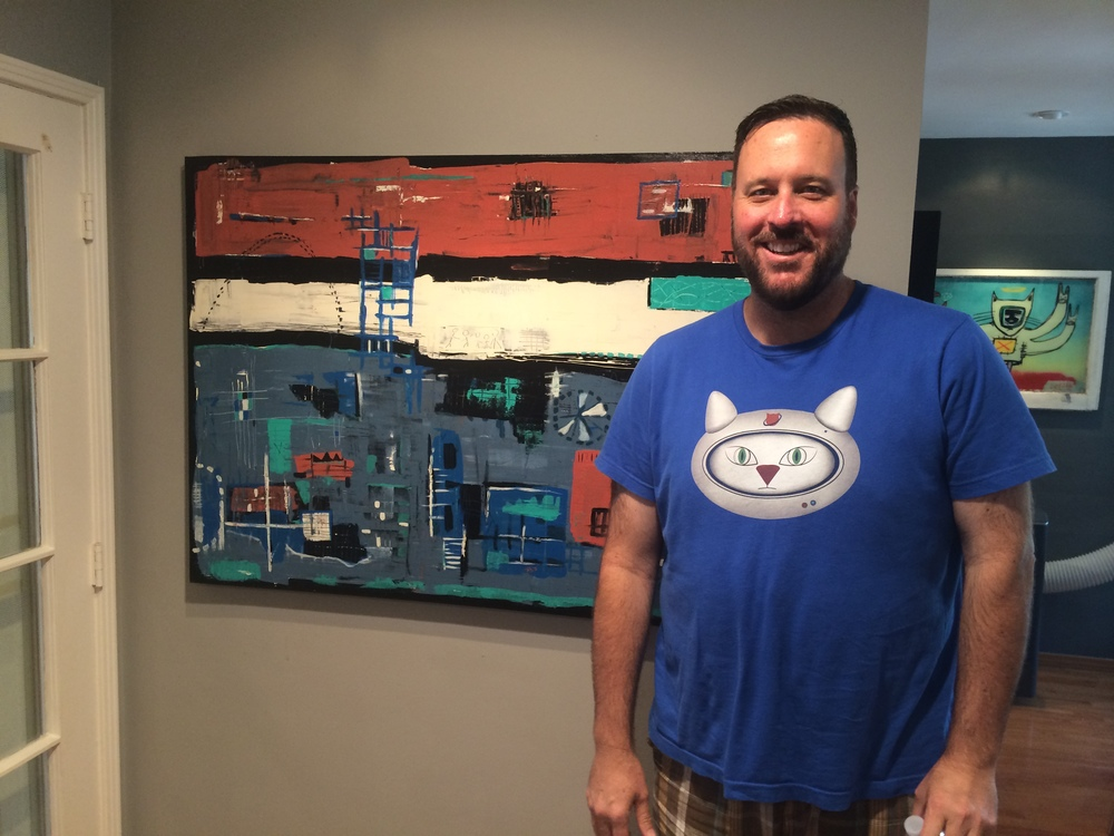 Joe Dietl in front of one of his paintings. The painting to the right is also one of his.