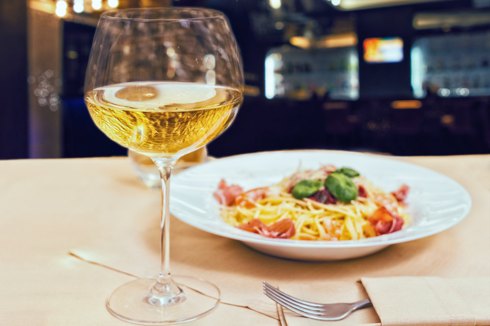 Close up of glass with wine near tasty spaghetti pasta in a rest