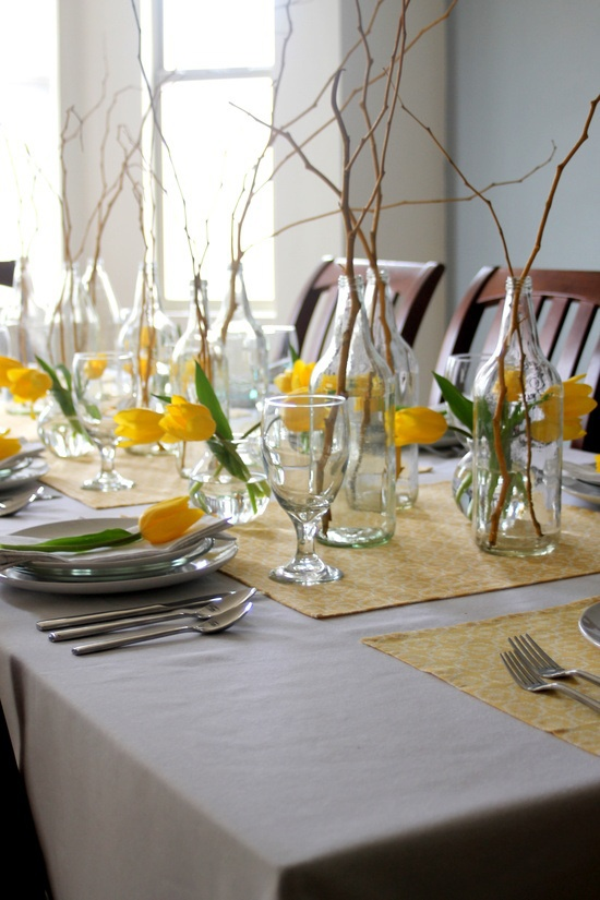 Simple yellow tulips and twigs dress up this Easter table without too much fuss. Idea via   30s Magazine  .