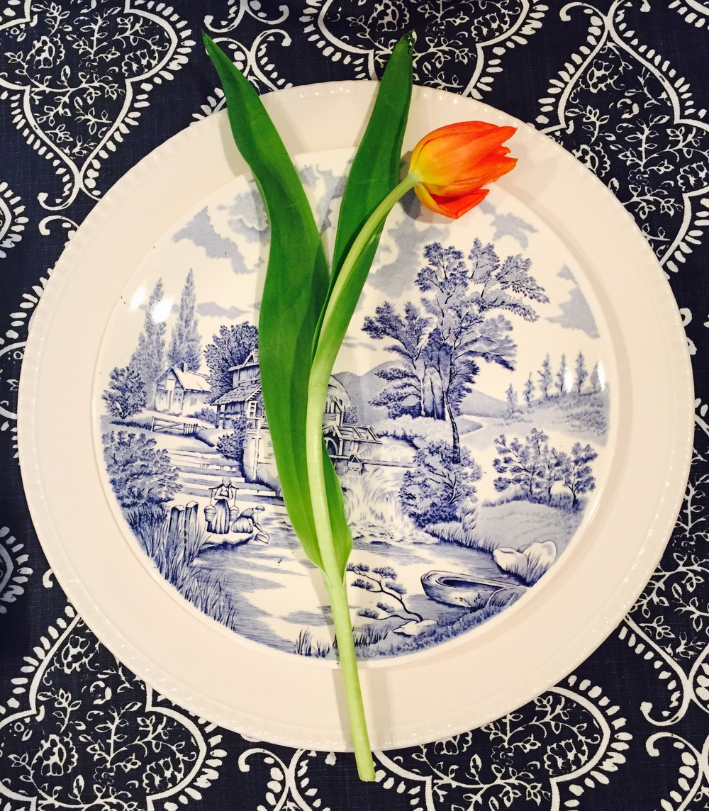 A simple orange tulip adds a perfect splash of color for those wanting a brighter table setting. Image via Jessica Gordon Ryan
