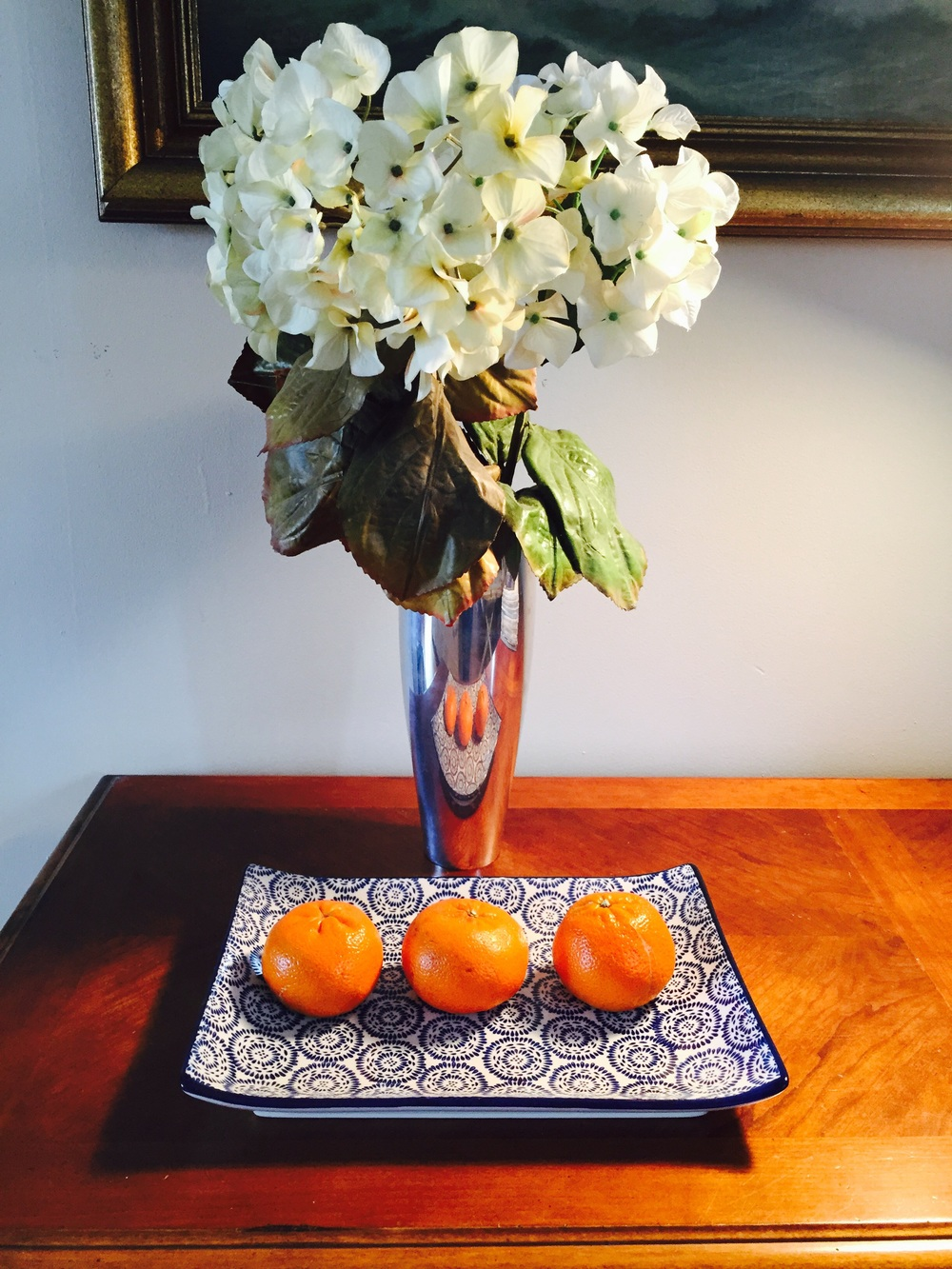 White hydrangea sit in a heavy metal Nambe vase that was a wedding gift nearly 20 years ago. It sits on a table beneath a beautiful oil painting of an angry Maine seacoast. A pretty but inexpensive rectangular plate that I picked up from Pier 1 last winter (simply because I loved the colors and pattern) serves as the perfect vessel for 3 flawless clementines. Note the hydrangea - they're not real! They're silk and from Pottery Barn and at least 15 years old. I'm not one for fake flowers, but every once in a while I spot a perfect fake flower... And these do the trick! If you haven't any fresh flowers at home, I might suggest you pick some up on the way home. I guarantee they'll make all the difference.