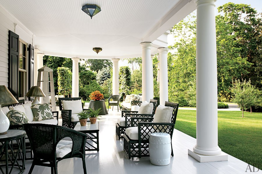 In this image of a Connecticut home featured in Architectural Digest, Miles Red creates a handsome and informal seating area using wicker furniture that once belonged to tobacco heir Doris Duke.