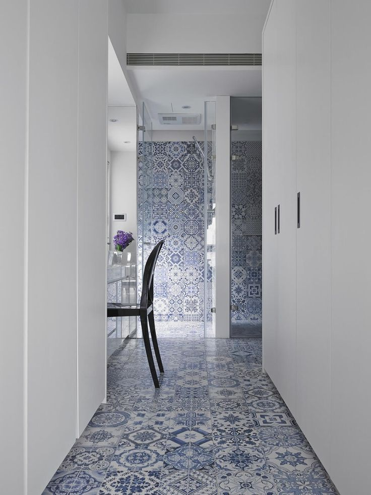 These blue and white tiles offer color, pattern and pop in contrast to the stark white walls and vanity area. Image via Home Adore.