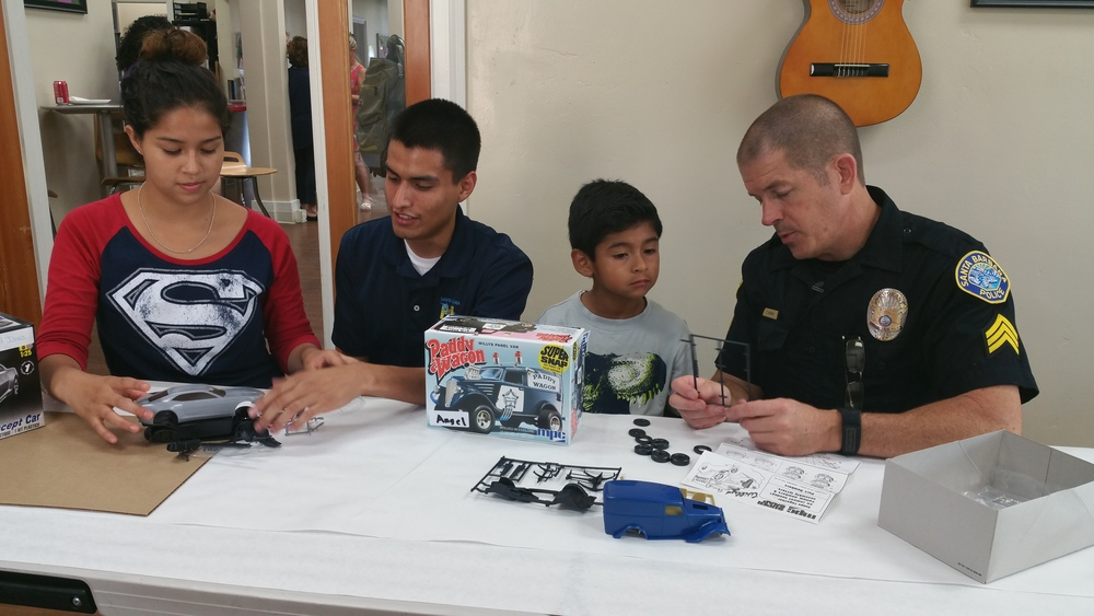 Officer Todd Johnson working with the local children on their car building skills.