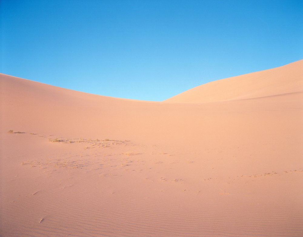 Eureka Sand Dunes right before Dusk, 2017. Pentax 6x7 + 55mm F/4. A late afternoon hike into these massive dunes was met with harsh sand blasting winds. Scared for the well being of the big pentax I was intending to not remove it from it's protective bag. After clearing the apex of a dune we came to this small valley which was calm and shield from the wind allowing me to take a few shots with the 6x7.