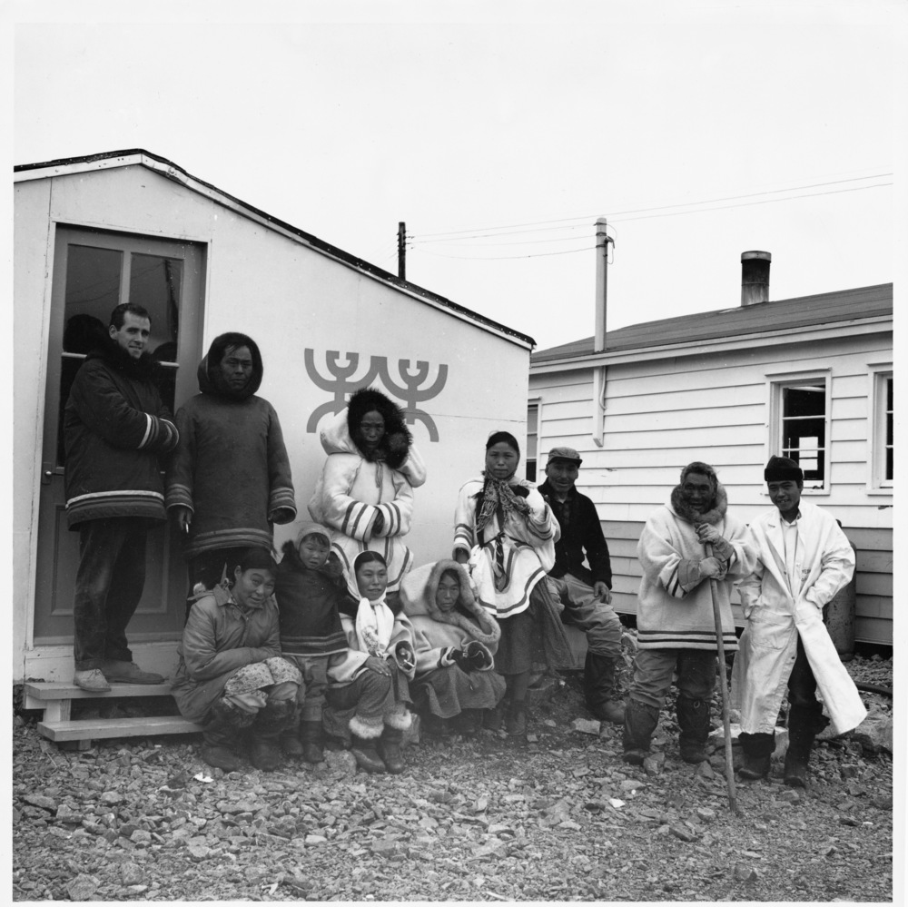 Terry Ryan and the early stable of artists in front of the print shop, 1961. Left to Right: Ryan, Publo Pudlat, Pitseolak Ashoona, Napachie Pootoogook, Kiakshuk, Parr, Joanasie Salomomie Seated Front: Eegyvadluk Ragee, Kenojuak Ashevak, Lucy Qinnuayuak. © National Film Board