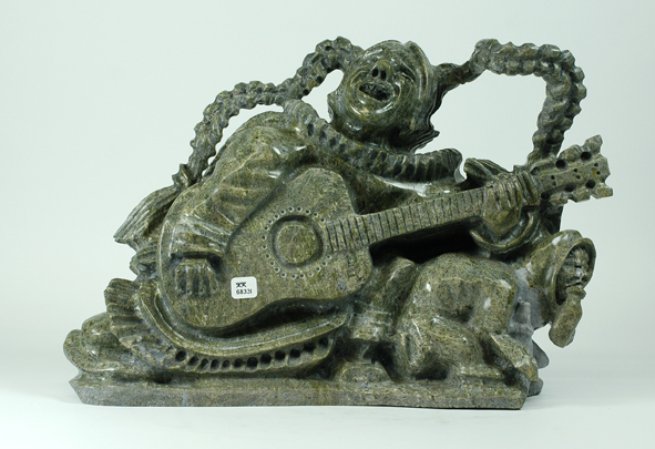 6838I  POOTOOGOOK JAW  WOMAN WITH GUITAR, 2014   Serpentine  H 11 x  W 15.5 x  D 6.5 in