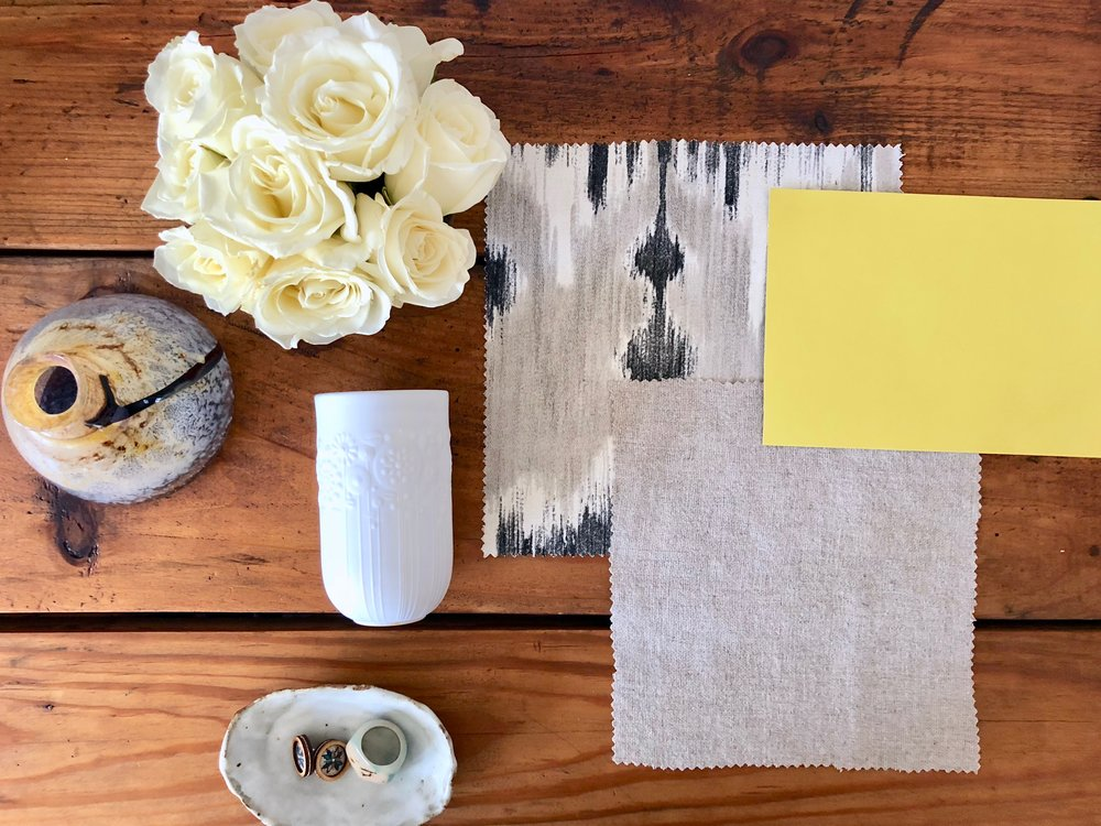 A mood board with fabric, flowers, and paint swatches for interior design