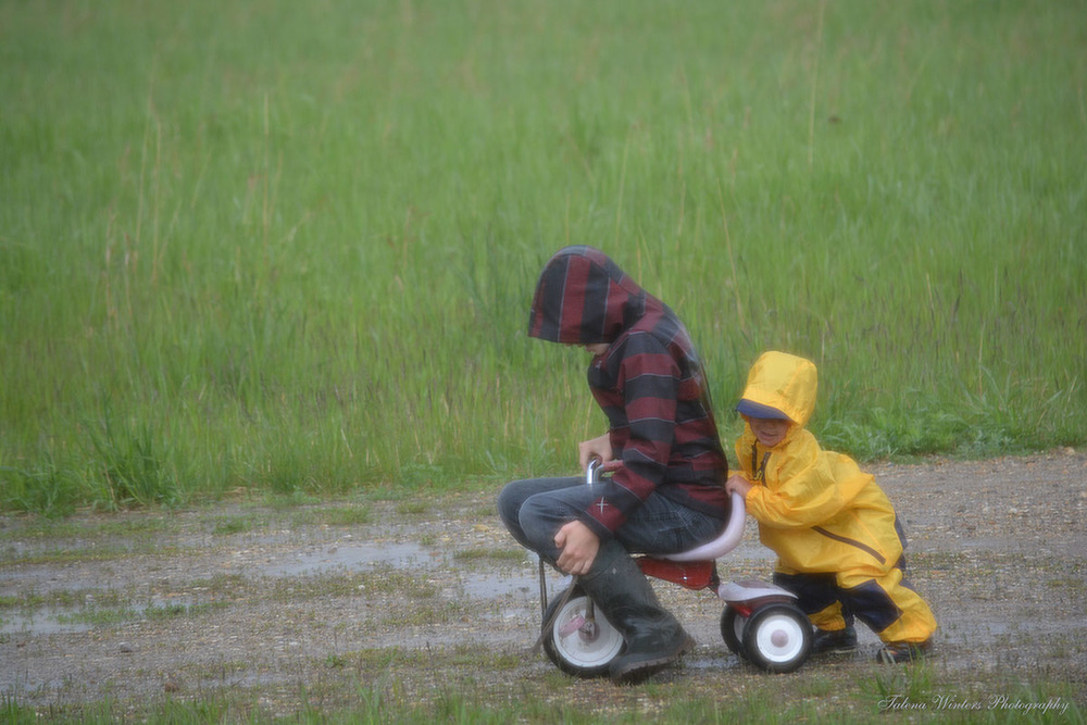 Last June, pushing Jude on his own tricycle. Yes, Levi's idea!
