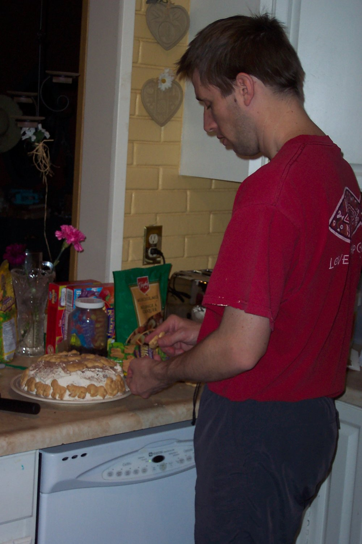 Jason decorating the cake with safari animal crackers.