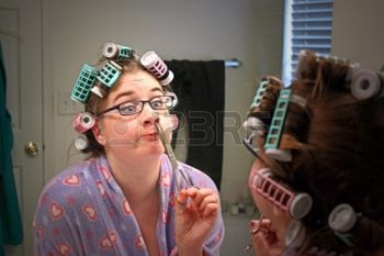 15764466-a-young-caucasian-girl-wearing-a-colorful-robe-curlers--and-glasses-makes-a-funny-face-while-she-tri.jpg