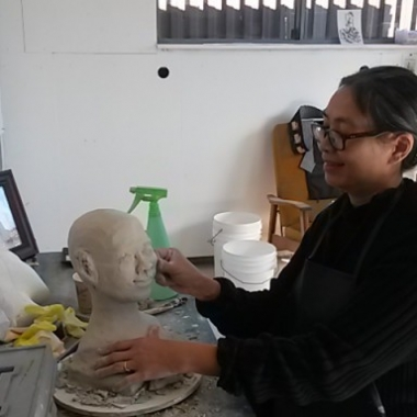 Phaptawan Suwannakudt in the studio working on a bust of her mother. (Image from belmoreitch.com)