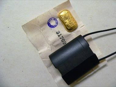 JAMES MCALLISTER (GUEST ARTIST)    Black Box (Wrapped Gold Ingot. 1oz/31.1gms)    2009   Black bakelite/gold/rice paper/linen thread/closure   43 x 40 mm