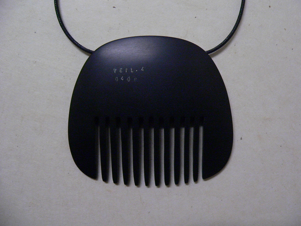 Slotted Panel (Comb). stamped with text. Veil 4 , 2009, Black bakelite, 70 x 80 mm