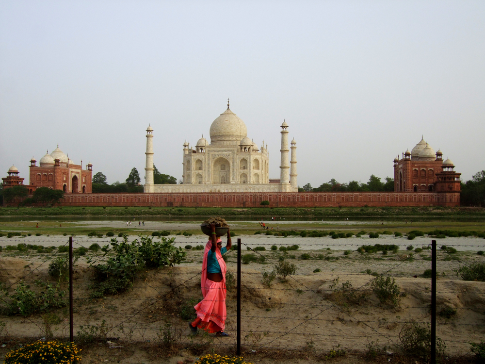 As the early evening light fades a woman carries a heavy load of cattle dung on her head while tourists pose for photos against the backdrop of the Taj Mahal.