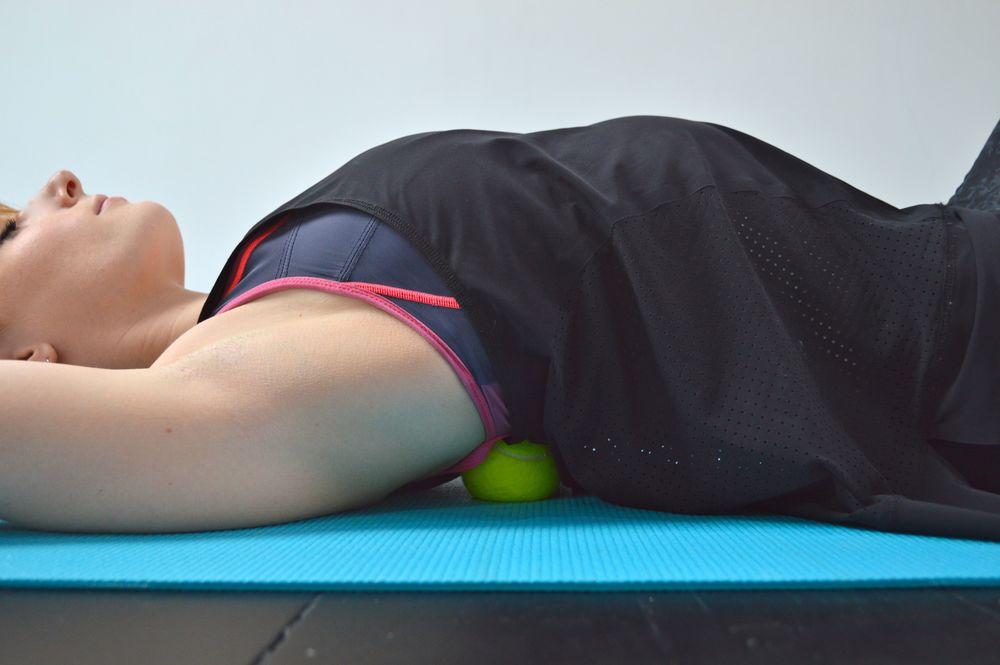 Place two tennis balls either side of the spine between the shoulder blades. Lie on the back and move around to massage into the muscles. Again, find those especially tender spots, and make small, mindful movements to explore the sensation. You can roll the tennis balls all the way from the top of the back to the bottom of the spine for a full back massage.