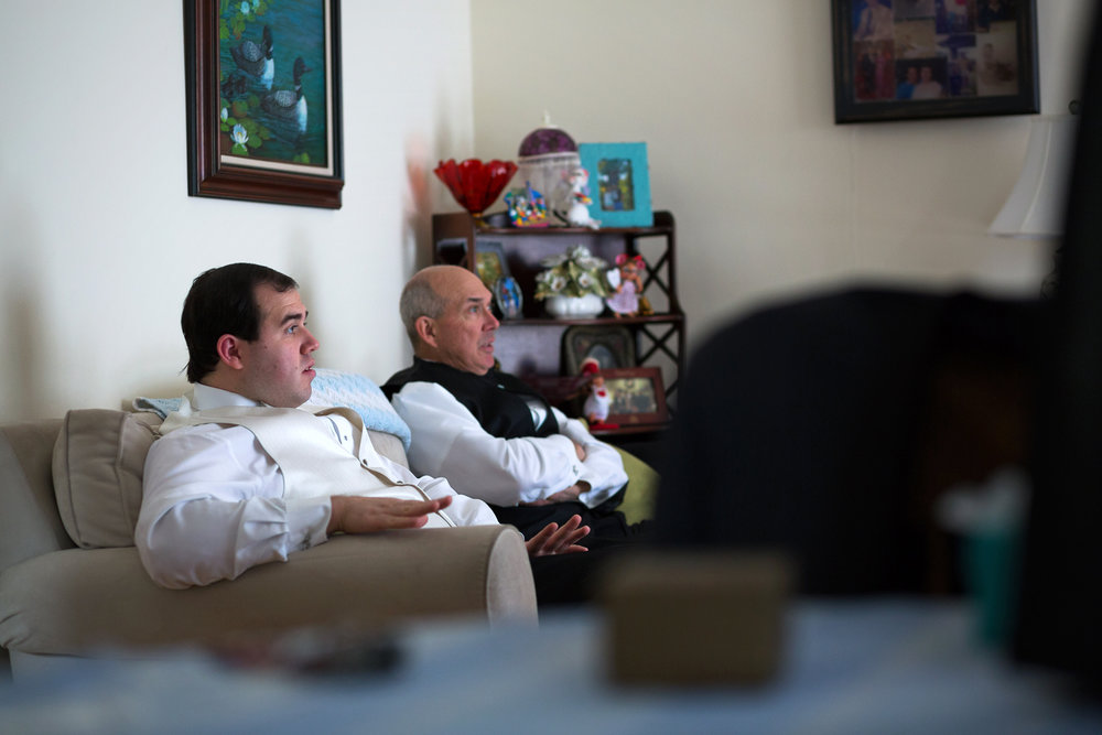 Groom and father watching TV together before wedding