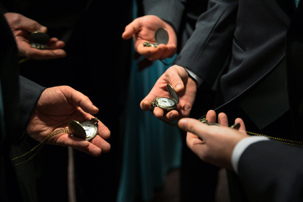 Groomsmen setting time on pocket watches before wedding