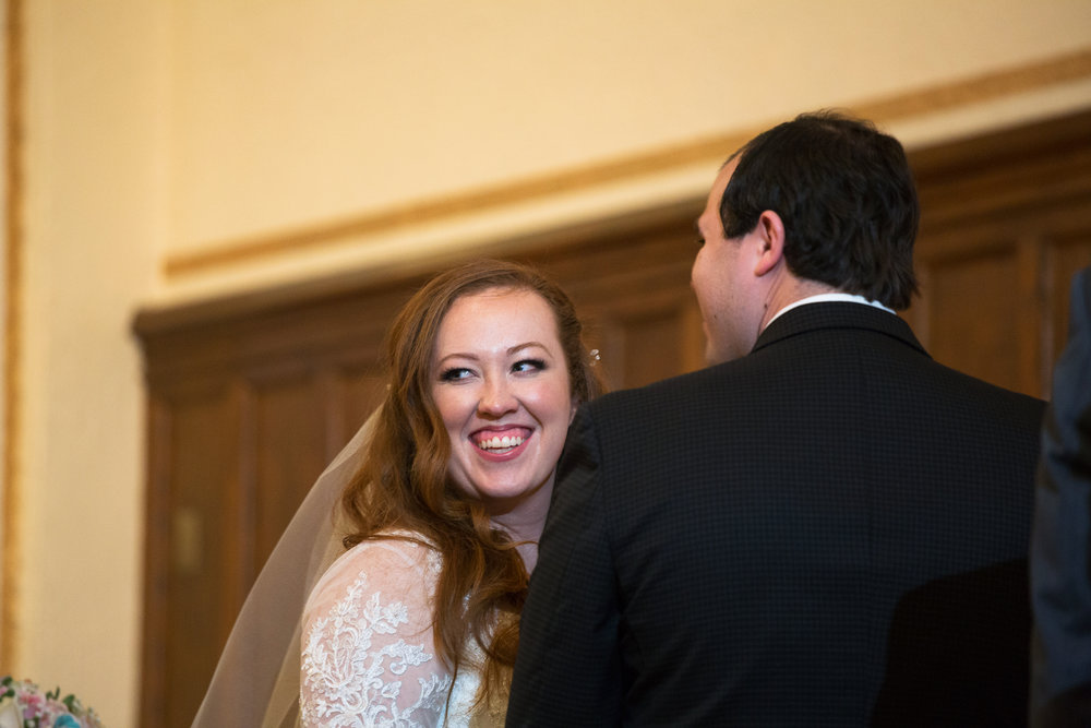 Bride laughing and looking back at audience during wedding