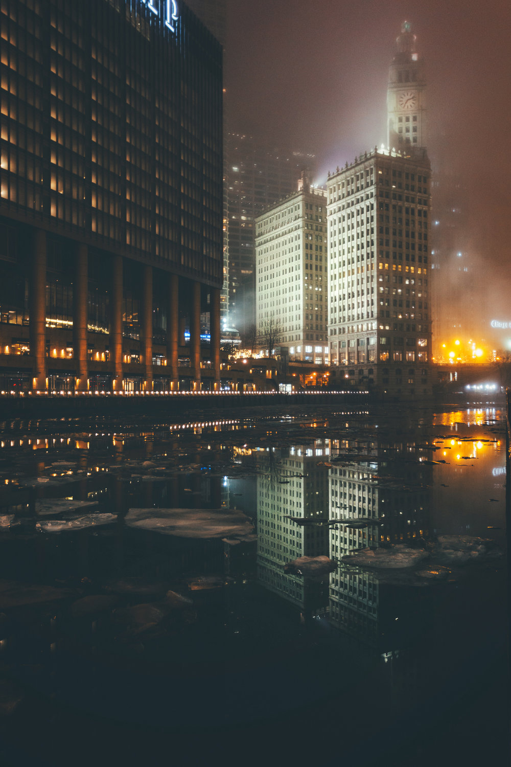 Building reflected in Chicago river with ice and fog