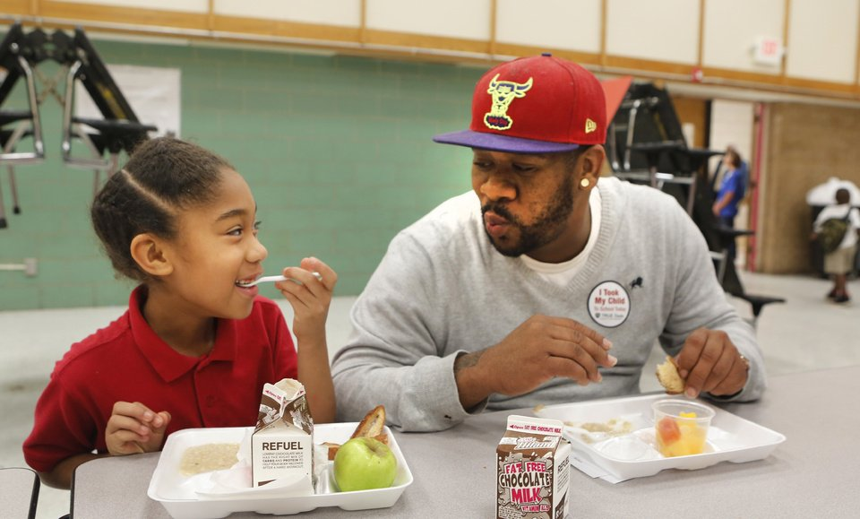 Below: Third-grader Gaybriana James and her dad, Gayland, eat breakfast Friday during Take Your Child to School Day at F.D. Moon Elementary School. Gayland James said he took off work to be there with his daughter.