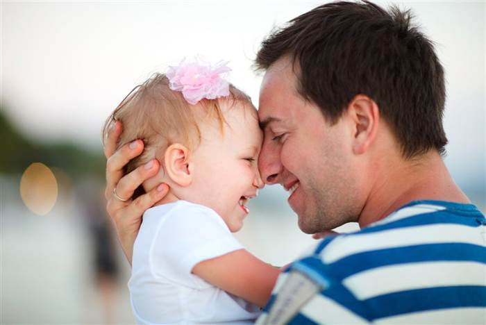 Dad hugging baby daughter.   Shutterstock