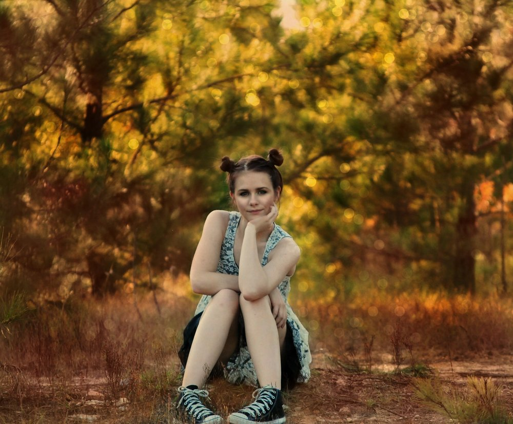 girl-sitting-posing-trees.jpg
