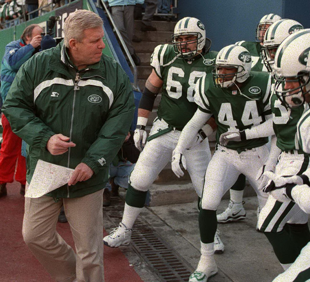 SI 's excerpt involving the Jets provides an opportunity to highlight one of my favorite photos in the book: Big Bill leads his cocksure, charged-up players, including center Kevin Mawae (#68) and special-teams ace Corwin Brown (#44), at the Meadowlands for their 1998 regular-season finale on December 27. Gang Green would trounce Pete Carroll's Patriots, 31-10, concluding a historic year highlighted by the franchise's first division title. Only a couple seasons removed from ignominy, the Jets took most of their club-record twelve victories by at least a touchdown, and strutted into the playoffs. Nevertheless, Bill Parcells, a so-called master motivator, relentlessly kept his players on edge. Gang Green defeated Tom Coughlin's Jaguars, 34-24, for its first postseason victory in 12 years before losing in the AFC Championship, 23-10, at Denver. This photo captures Bill's leadership and determination and perhaps even the galvanizing gifts that had enabled him to transform multiple franchises.     Thomas E. Franklin , Bergen Record