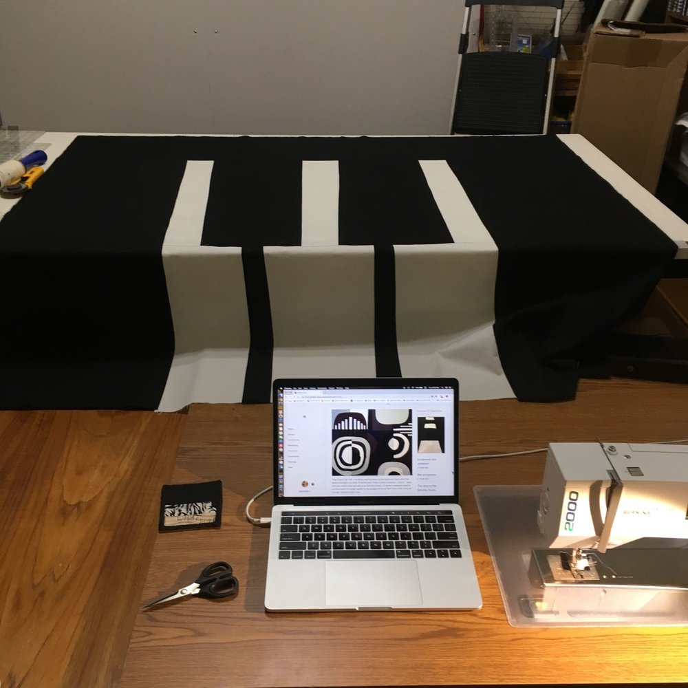 "This is my workspace. I pulled up my blog on my Macbook Pro and that's my trusty Bernina 160 (circa 2000) on the right. I had just finished sewing and ironing the top piece of the ""keys."""
