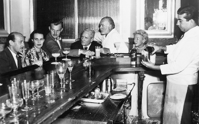 Hemingway (center, white shirt) enjoying his cocktail namesake at El Floridita with actor Spencer Tracy just in front of him