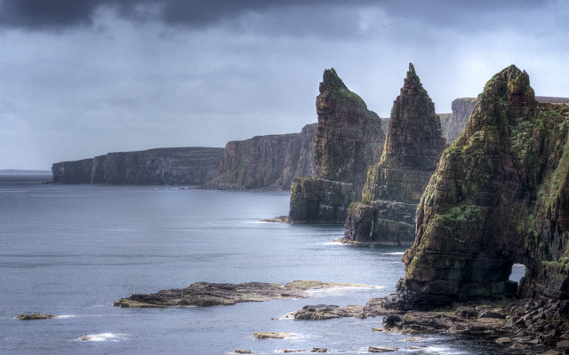 These dramatic rock formations known as the Duncansby Stacks reach heights of 60 meters, taller than the cliffs from which they broke off millions of years ago, with The Great Stack situated 200 meters from the shoreline.