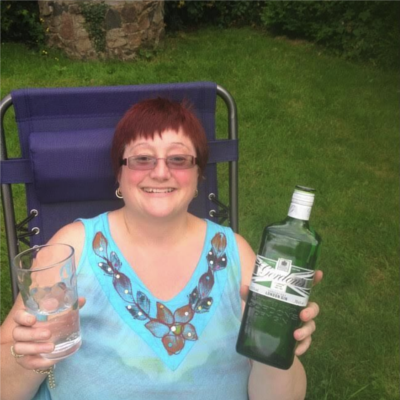 Tracy with her homemade gin, stored in a bottle of Gordons.