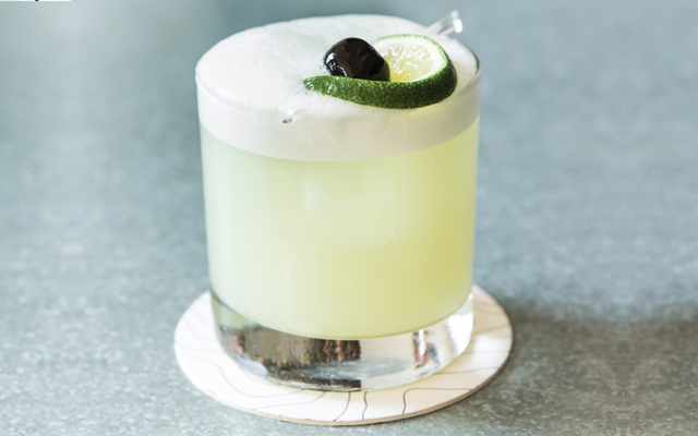 Green eyed gin cocktail with lime and cherry