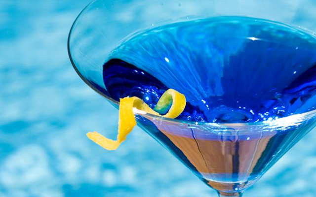 Blue hued gin cocktail with lemon zest