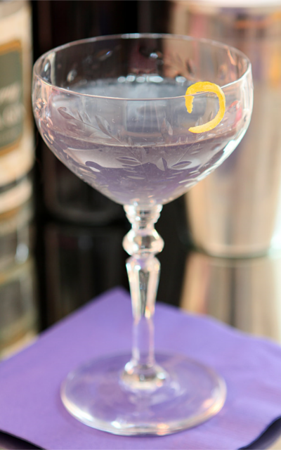 Violet liqueur creme blue moon gin cocktail with lemon zest