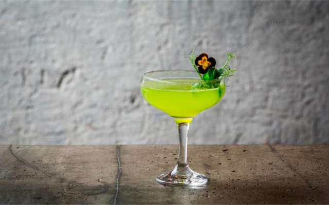 Peas and mint bright green cocktail in martini glass with gin and edible flowers to garnish