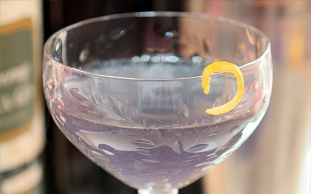 Purple cocktail in martini glass with lemon zest peel