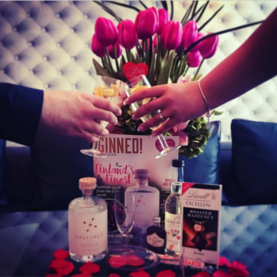 Roses in a vase with ginned magazine and gin bottle with chocolate cheersing on valentines day