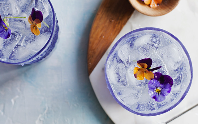 Purple fleur collins cocktail with edible flowers
