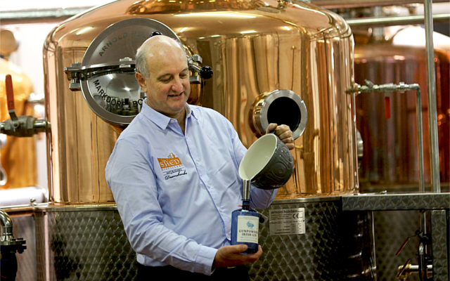 Distiller pouring gin into bottle in front of copper still