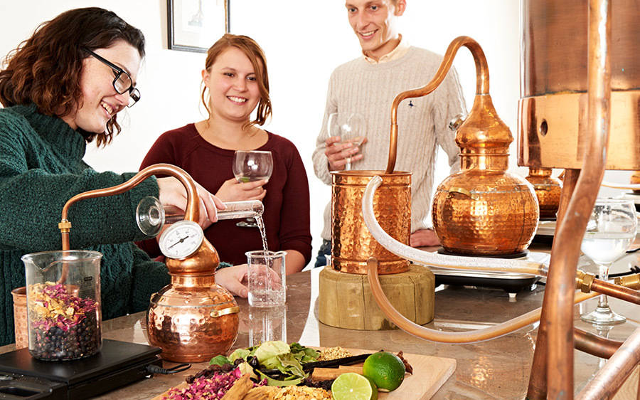 Gin making at a distillery with copper still and botanicals