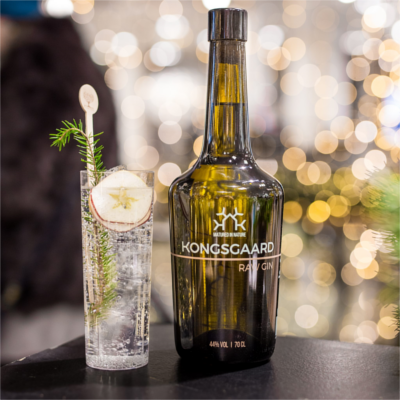 Kongsgaard Gin and gin and tonic with slice of apple and rosemary sprig to garnish with bokeh effect lighting in background