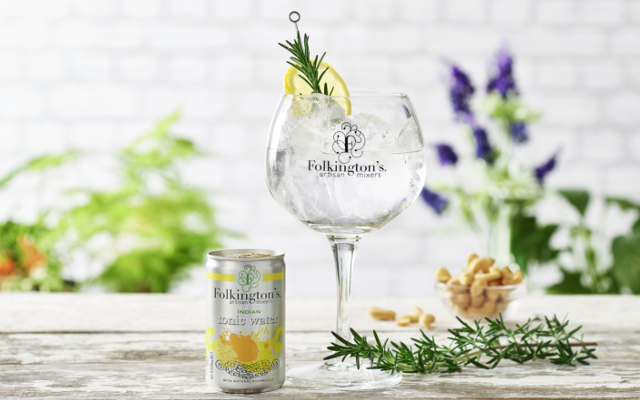 Folkington's tonic water can and gin and tonic in copa glass over ice with lemon and rosemary to garnish