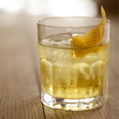 White gin negroni in tumbler with twist of lemon garnish