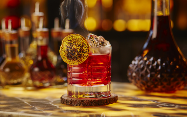 Negroni cocktail with dried lemon wheel garnish in tumbler